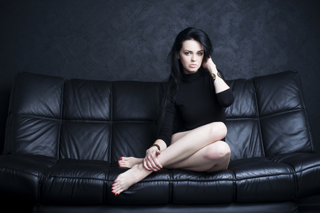 sexuel: Belle jeune femme avec de longues jambes dans body assis sur un canapé noir Banque d'images