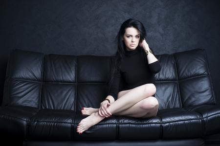 descansando: Mujer joven hermosa con las piernas largas en traje sentado en un sof� negro