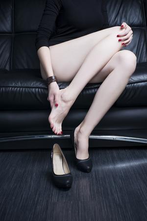 beautiful feet: Beautiful young woman with long legs in bodysuit sitting on a black sofa. Leg pain