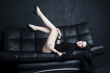 Beautiful young woman with long legs in bodysuit sitting on a black sofa Фото со стока - 47556239
