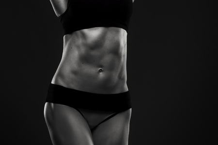 black and white photography: Attractive fitness woman in studio. Muscular abdomen close-up. Trained female body. Black and white photography