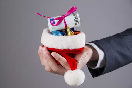christmas budget: Businessman holding Santa hat with money on gray background Stock Photo