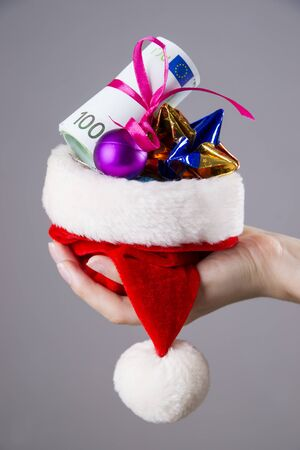 contributions: Santa hat with money in woman hands on gray background