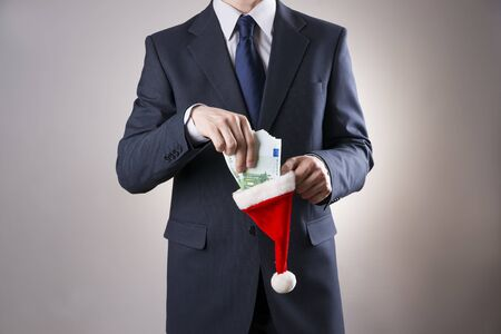 christmas budget: Businessman putting money in a Santa hat on gray background