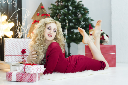 Beautiful woman in a red dress with many gift boxes. Christmas concept Stock Photo