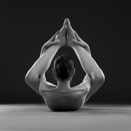 nackt: Naked Yoga. Sch�ne reizvolle Karosserie der jungen Frau auf grauem Hintergrund. Low key schwarz und wei� Studiofotografie Lizenzfreie Bilder