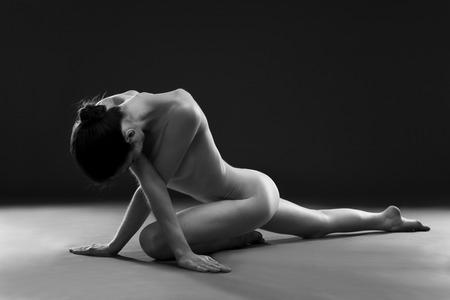 mujer desnuda sentada: Yoga desnudo. Carrocería atractiva hermosa de la mujer joven en el fondo gris. Bajo llave blanco y negro fotografía de estudio