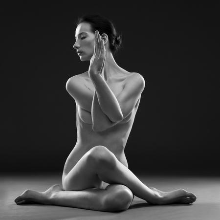 femme noire nue: Yoga nu. Belle corps sexy de jeune femme sur fond gris. Discret en noir et blanc photographie de studio Banque d'images