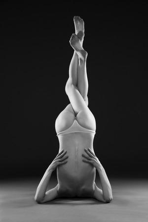 schwarze frau nackt: Naked Yoga. Sch�ne reizvolle Karosserie der jungen Frau auf grauem Hintergrund. Low key schwarz und wei� Studiofotografie Lizenzfreie Bilder