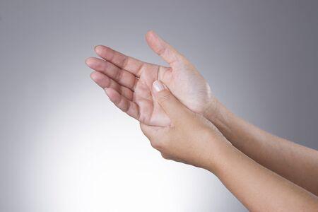 persona enferma: Dolor en las articulaciones de las manos sobre un fondo gris. Foto de archivo