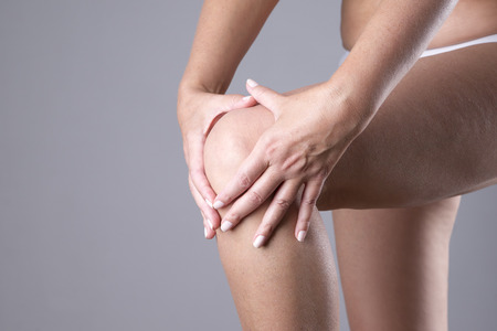 masaje deportivo: Dolor en la rodilla en un fondo gris