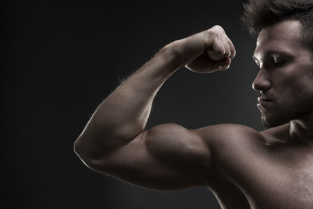 brawn: Handsome muscular bodybuilder posing on gray background.