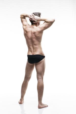 Handsome muscular bodybuilder posing on white background.