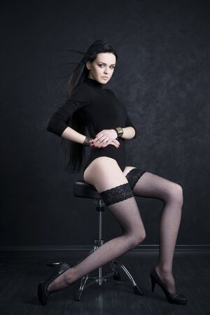 Beautiful young woman in stockings and in bodysuit with long legs and long black hair sitting on a chair on a black studio background. Stock Photo