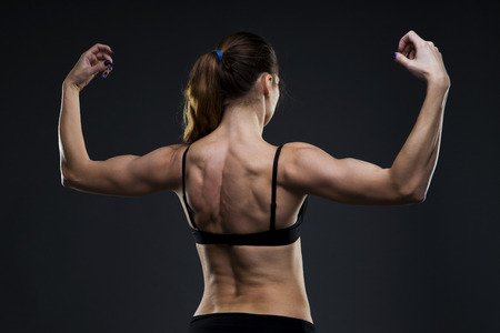 muscled: Attractive fitness woman on gray background in studio. Muscular back close-up.