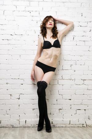 girls in panties: Young beautiful sexy woman posing in lingerie near a white brick wall. Studio shot Stock Photo