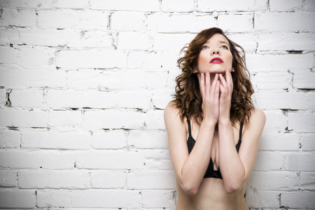 nude female body model: Young beautiful sexy woman posing in lingerie near a white brick wall. Studio shot Stock Photo