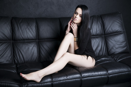 woman on couch: Beautiful young woman in bodysuit with long legs and long black hair sitting on a black sofa. Studio shot Stock Photo