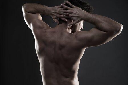 dorsi: Handsome muscular bodybuilder posing on gray background.