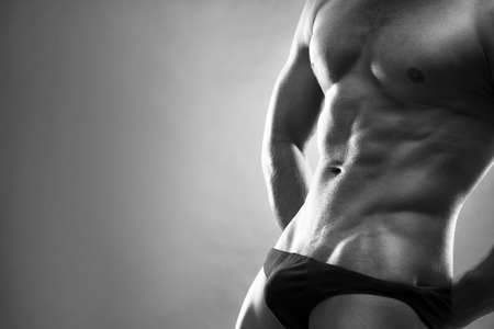 modelos hombres: Culturista musculoso guapo posando sobre fondo gris. Bajo estudio blanco y negro tiro clave con copia espacio. Cuerpo masculino atractivo