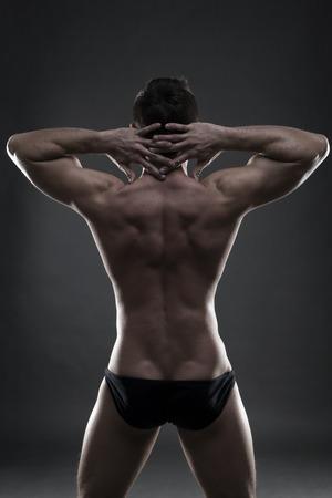 male silhouette: fisicoculturista muscular hermoso que presenta en fondo gris. tiro bajo estudio clave. cuerpo masculino atractivo
