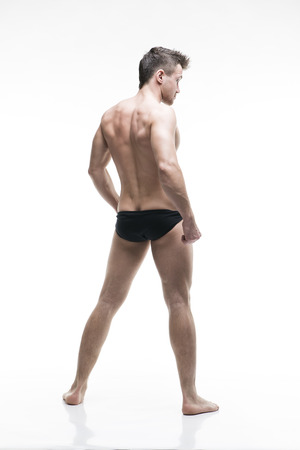muscle building: Handsome muscular bodybuilder posing on white background. Isolated studio shot. Sexy male body