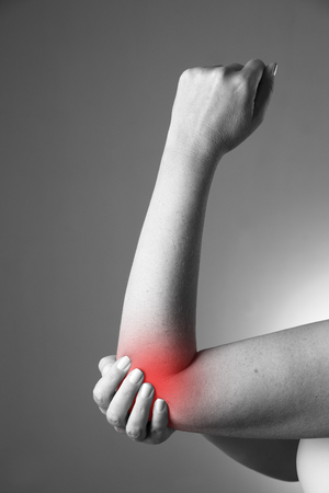 enhanced healthy: Pain in the joints of the hands. Pain in the human body on a gray background. Black and white photo with red dot