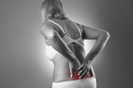back strain: Woman with backache. Pain in the human body on a gray background. Black and white photo with red dot