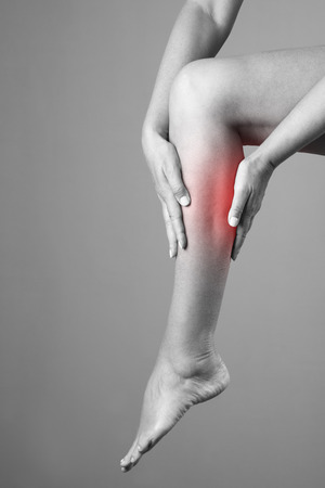 calf pain: Pain in the calf muscle of the woman. Massage of female feet. Pain in the human body on a gray background. Black and white photo with red dot