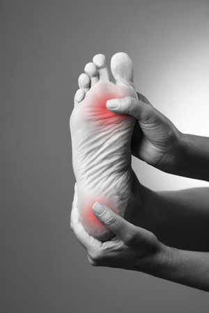 Pain in the foot. Massage of female feet. Pain in the human body on a gray background. Black and white photo with red dot Фото со стока