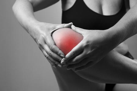 Schmerzen im Knie. Schmerz im menschlichen Körper auf einem grauen Hintergrund. Schwarz-Weiß-Foto mit red dot Standard-Bild