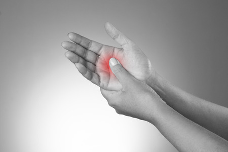 carpal tunnel: Pain in the joints of the hands. Carpal tunnel syndrome. Pain in the human body on a gray background. Black and white photo with red dot Stock Photo