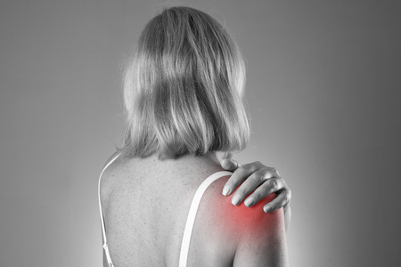shoulder inflammation: Woman with pain in shoulder. Pain in the  human body on a gray background. Black and white photo with red dot Stock Photo