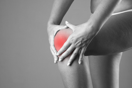 woman pain: Pain in the knee. Pain in the human body on a gray background. Black and white photo with red dot Stock Photo