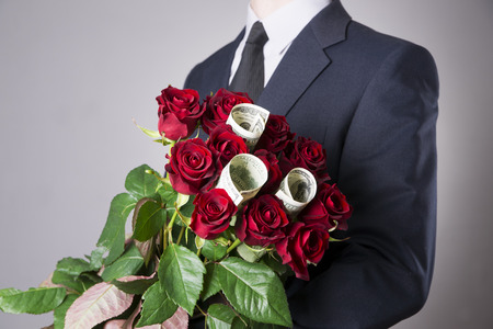 red hand: Man with bouquet of red roses on a gray background. Present at the International Womens Day