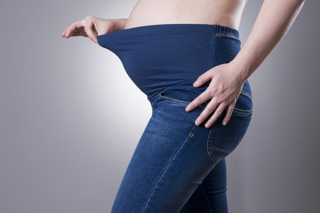 pregnant jeans: Pregnant woman in blue jeans for pregnant women on gray background. Side view Stock Photo