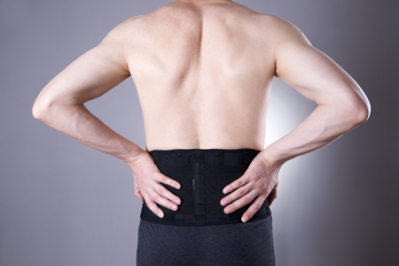 Man with a medical belt for the back on a gray background. Studio shot Banque d'images