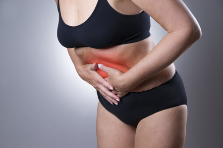 ovario: Mujer con dolor abdominal. Dolor en el cuerpo humano sobre un fondo gris con el punto rojo