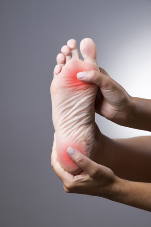Pain in the foot. Massage of female feet. Pain in the human body on a gray background with red dot Фото со стока - 53023573