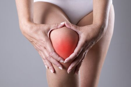 stretching condition: Pain in the knee. Pain in the human body on a gray background with red dot