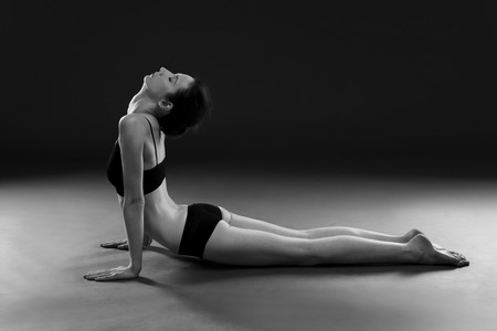 nude gymnast: Yoga asana. Beautiful sexy body of young woman on black background