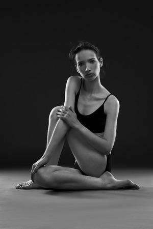 mujer desnuda sentada: asanas de yoga. Carrocería hermosa de la mujer joven en el fondo negro