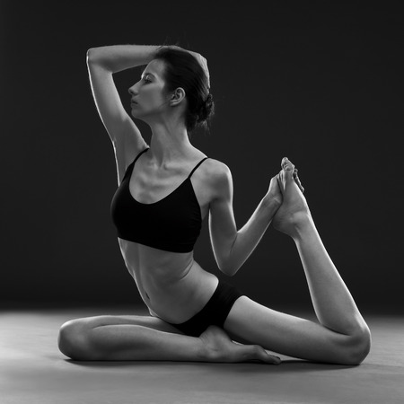 nude woman sitting: Yoga asana. Beautiful sexy body of young woman on black background