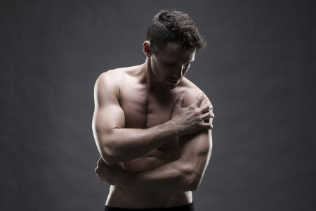 enhanced healthy: Pain in the shoulder. Muscular male body. Handsome bodybuilder posing on gray background. Low key close up studio shot. Middle part of the body