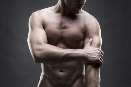 muscular body: Pain in the elbow. Muscular male body. Handsome bodybuilder posing on gray background. Low key close up studio shot. Middle part of the body Stock Photo