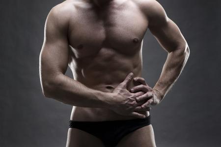dolor de pecho: Dolor en el lado izquierdo del cuerpo masculino muscular. Guapo fisicoculturista posando sobre fondo gris. cierre encima del tiro bajo estudio clave. La parte media del cuerpo Foto de archivo