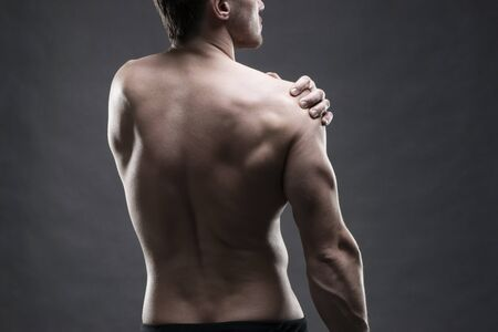 broken back: Pain in the shoulder. Muscular male body. Handsome bodybuilder posing on gray background. Low key close up studio shot. Middle part of the body