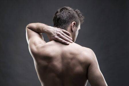 soreness: Pain in the neck. Man with backache. Muscular male body. Handsome bodybuilder posing on gray background. Low key close up studio shot. Middle part of the body