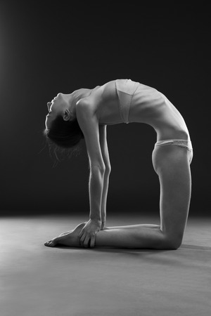 nude woman sitting: Naked yoga. Beautiful sexy body of young woman on gray background. Low key black and white studio photography Stock Photo