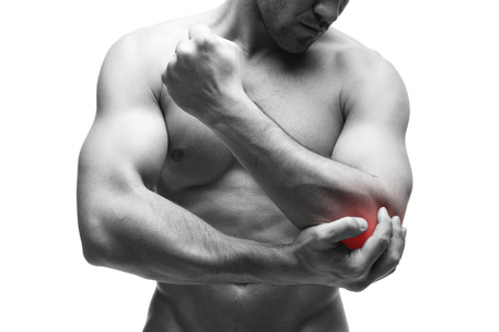 enhanced health: Pain in the elbow. Muscular male body. Handsome bodybuilder posing in studio. Isolated on white background with red dot. Black and white photography